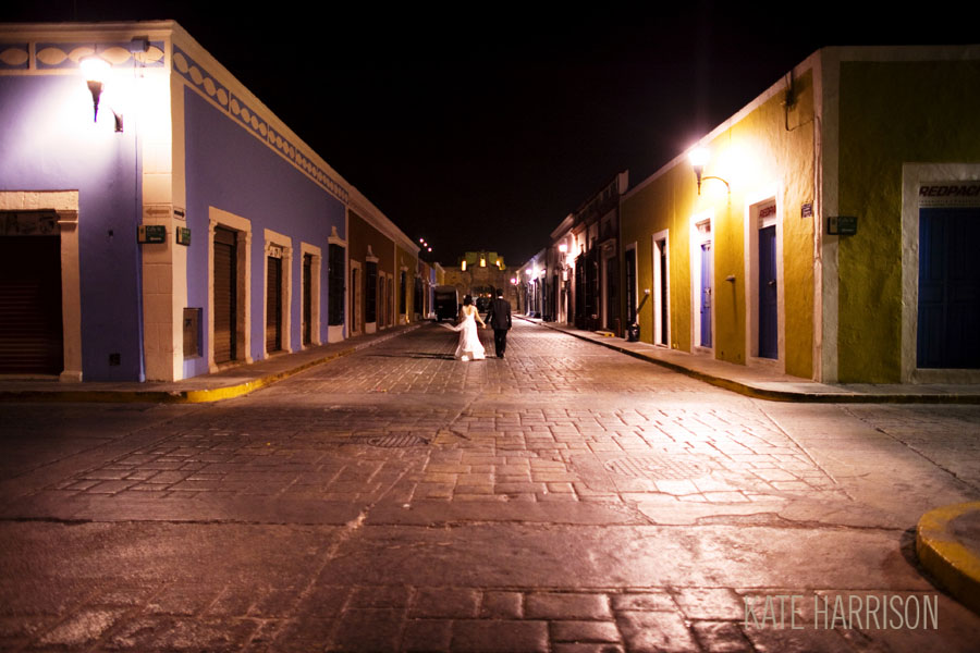 Wedding couple walking by colorful buildings at a Mexico destination wedding Destination wedding planner, Mango Muse Events