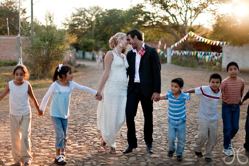 Wedding couple with local kids at a Mexico destination wedding Destination wedding planner, Mango Muse Events