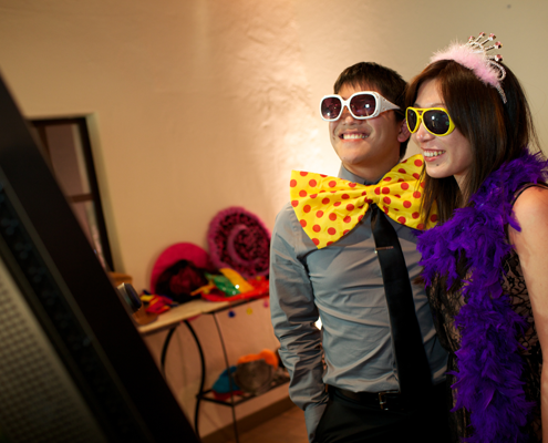 Couple taking a wedding photobooth photo by Destination wedding planner, Mango Muse Events