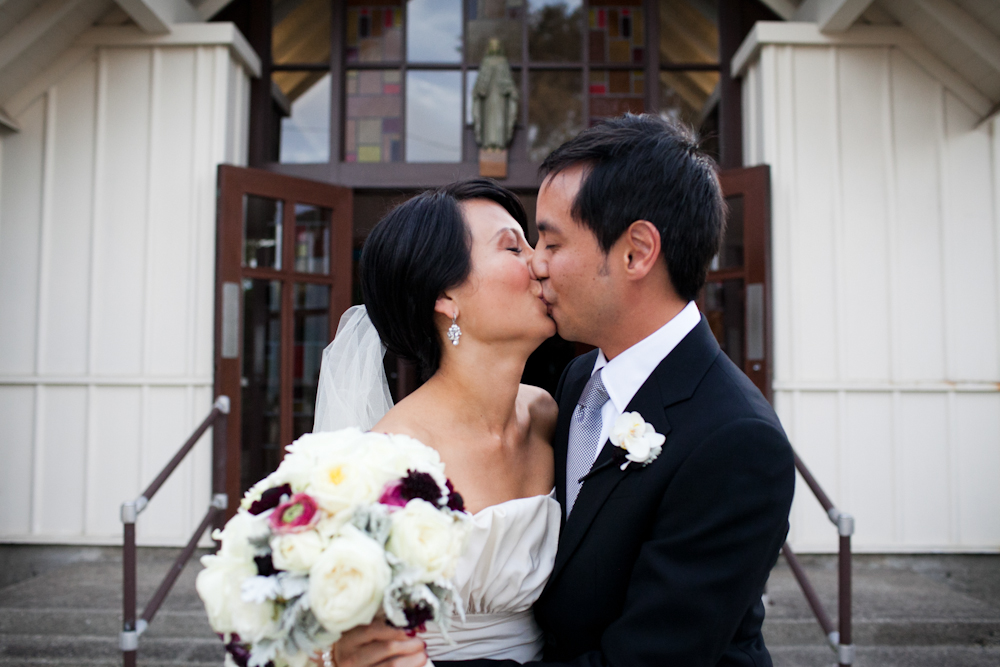 Newly married couple kissing in front of Chapel of Our Lady at a San Francisco wedding by Destination wedding planner Mango Muse Events
