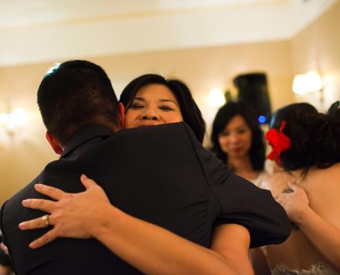 Wedding couple hugging wedding guests at a destination wedding in lieu of a wedding reception line