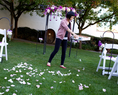 Wedding floral designer scattering flower petals for a wedding ceremony one of many wedding vendors for a wine country wedding by Destination wedding planner Mango Muse Events