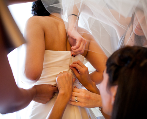 Bride getting into her wedding dress at her San Francisco wedding by Destination wedding planner Mango Muse Events