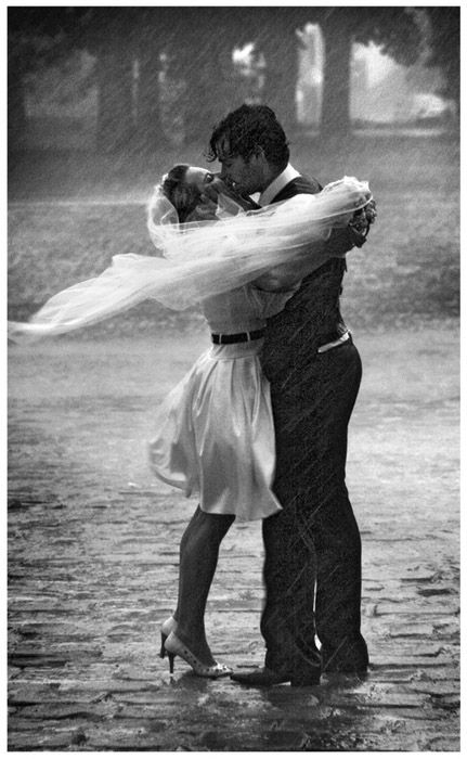 Wedding couple kissing in the rain at their rainy wedding.