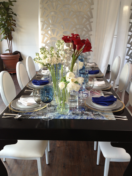 Wedding table decor using white and black florals, blue napkins and a black table by destination wedding planner Jamie Chang of Mango Muse Events.