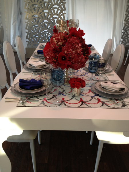 Wedding table decor using red florals, blue napkins and a white table by destination wedding planner Jamie Chang of Mango Muse Events.