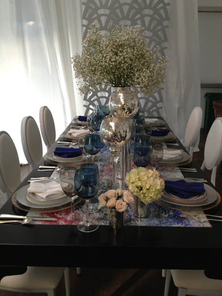 Wedding table decor using white florals, blue napkins and a black table by destination wedding planner Jamie Chang of Mango Muse Events.