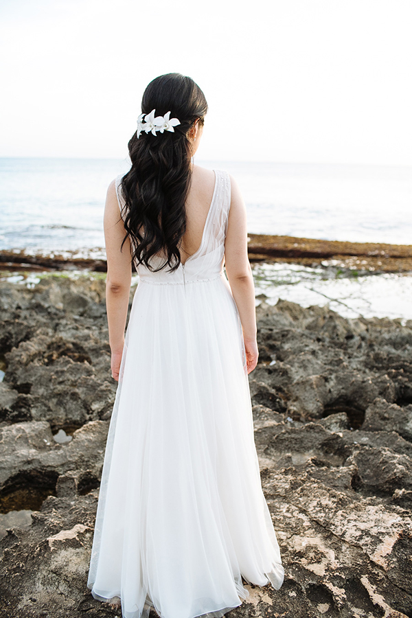 Bride with hair flowers at her wedding in Hawaii by Jamie Chang destination wedding planner of Mango Muse Events.