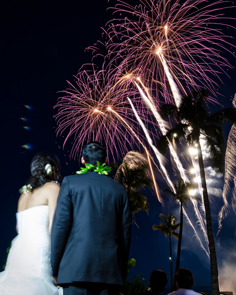 Couple stands outside watching the wedding fireworks after their destination wedding reception in Hawaii. Event design by destination wedding planner Jamie Chang of Mango Muse Events.