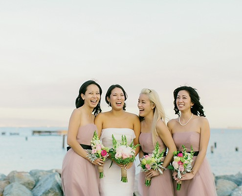Bride and bridesmaids smiling after wedding ceremony planned by Jamie Chang destination wedding planner of Mango Muse Events.