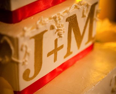 Wedding cake with red satin ribbon.