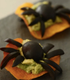 Black widow spider bites. A Halloween snack made with black olives and guacamole.