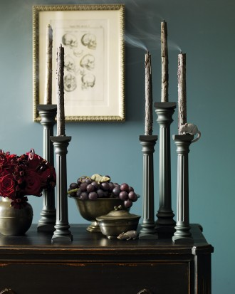 Gothic style candlesticks with black candles as Halloween decor.