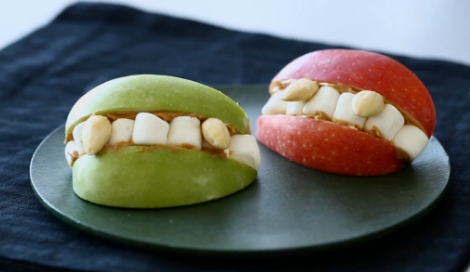 Halloween Vampire lips party treat made out of apples, peanut butter, marshmallows and nuts.