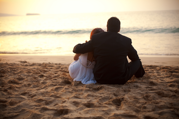 Newly married couple sitting on the beach watching a sunset at their destination wedding in Maui planned by Jamie Chang destination wedding planner of Mango Muse Events.
