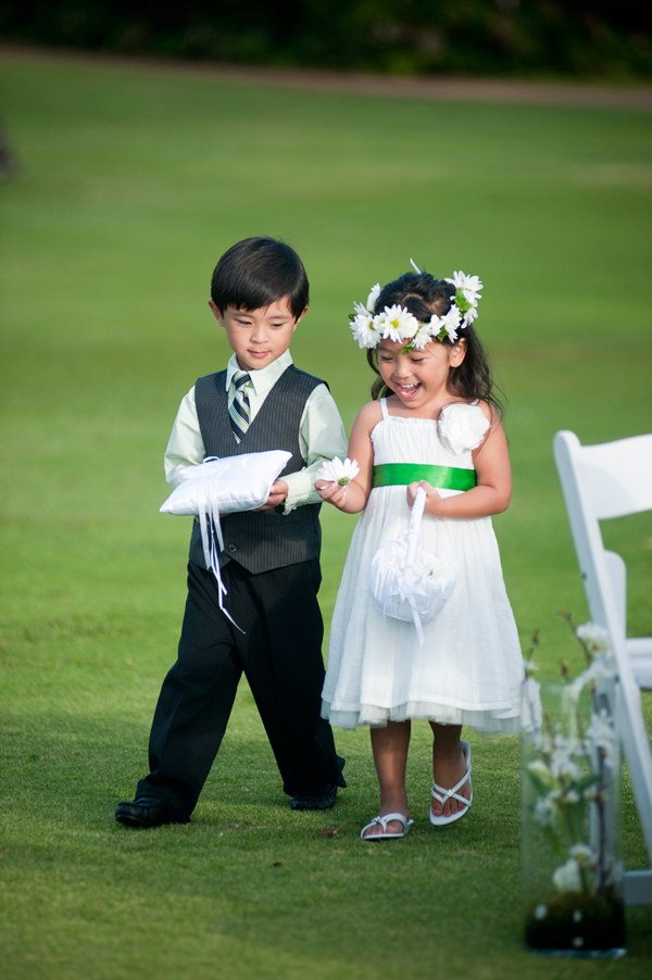 Flower girl and ring bearer walk down the aisle at a destination wedding in Lanikuhonua, Hawaii. Event design by Jamie Chang destination wedding planner of Mango Muse Events.