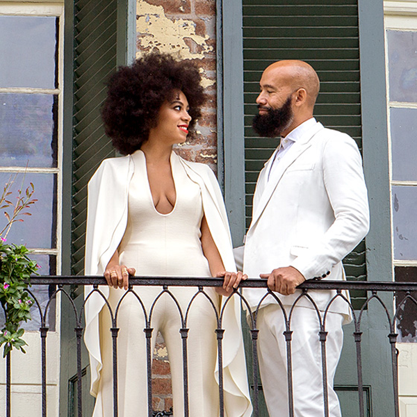Solange and Alan standing outside on a balcony at their New Orleans destination wedding