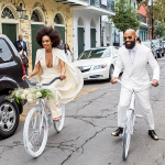 Solange and Alan riding bicycles at their destination wedding in New Orleans.