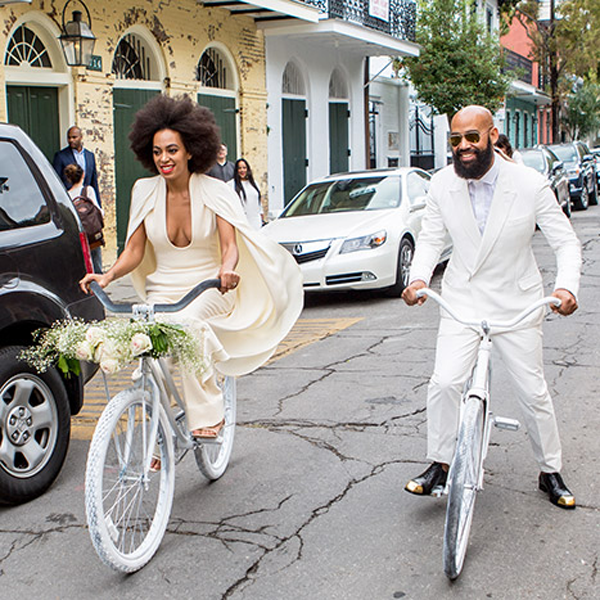 Solange and Alan riding bicycles at their New Orleans destination wedding