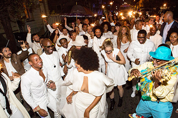 Solange dancing in the street of New Orleans with her wedding guests at a New Orleans destination wedding
