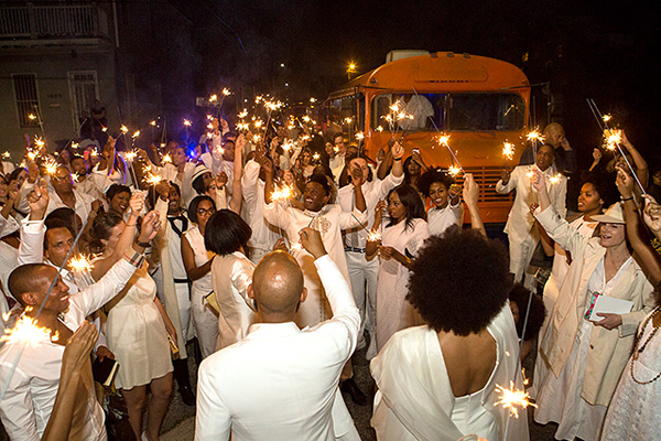Solange , Alan and wedding party guests holding sparklers at their New Orleans destination wedding