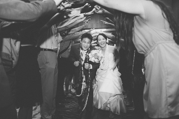 Couple walking under family and friends arm tunnel at their wedding send off at the end of their destination wedding in Hawaii by Jamie Chang destination wedding planner of Mango Muse Events.