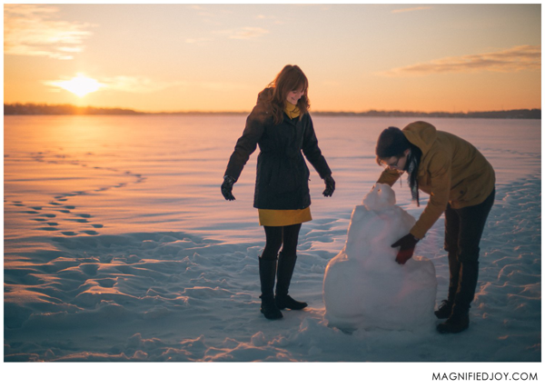 Engaged couple playing in snow taking sunrise photos for their engagement photo shoot.
