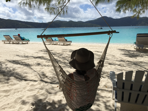 Jamie Chang destination wedding planner of Mango Muse Events relaxing in a hammock in the shade on the beach of Guana, a destination wedding location in the Caribbean.