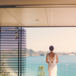 Bride staring out the window after getting ready for her wedding ceremony.