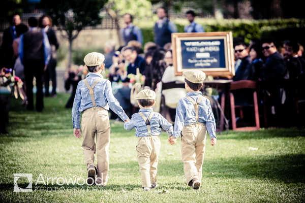 Ring bearers walking down the aisle to the processional ceremony songs at a destination wedding at Cornerstone in Sonoma by Jamie Chang destination wedding planner of Mango Muse Events.