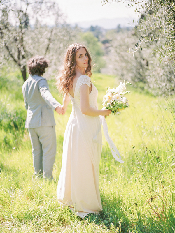 Newlyweds walking in the orchards at Villa Agapa, a destination wedding venue in Italy.