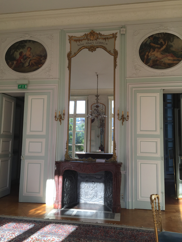 Mirror and fireplace in an upstairs room at the La Maison de Polytechniciens a destination wedding venue in Paris