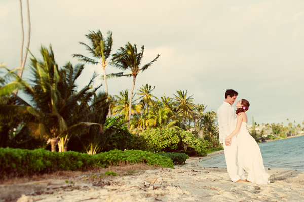 Bride and groom at the beach wedding in Hawaii by destination wedding planner, Mango Muse Events