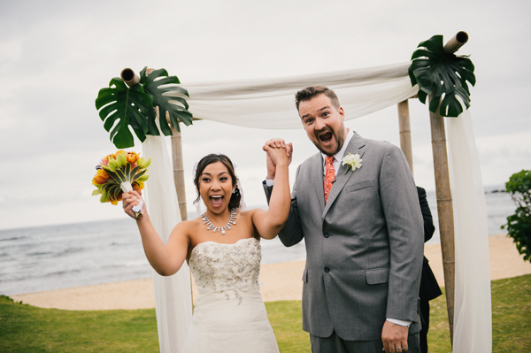An excited couple just after they are pronounced husband and wife at a Hawaii destination wedding by destination wedding planner, Mango Muse Events
