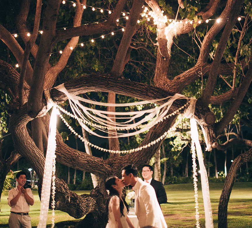 Bride and groom kiss at their night time wedding ceremony in Hawaii by Destination wedding planner Mango Muse Events