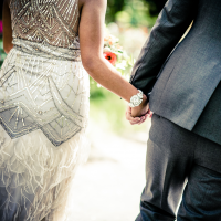 An wedding couple holding hands at their Sonoma destination wedding reflecting their unique wedding style