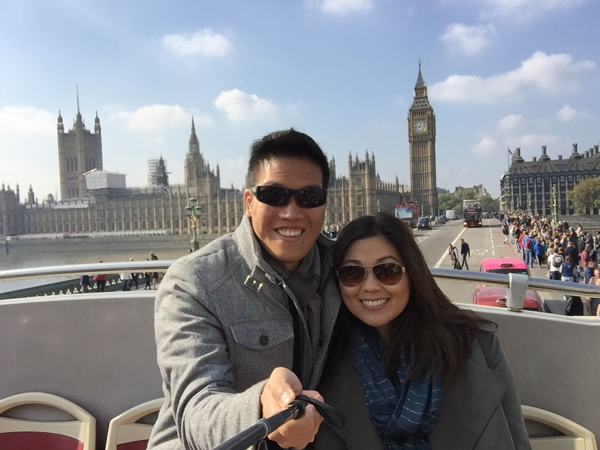 A couple taking a selfie with Big Ben using a selfie stick in London, England