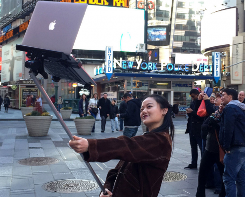 Girl with a macbook selfie stick in Times Square, New York