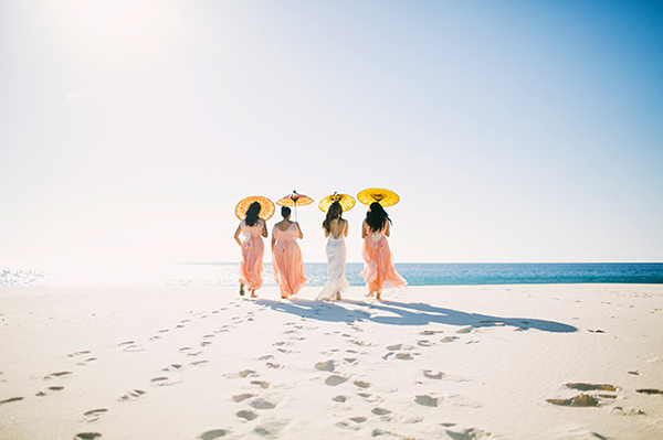 Bride and bridesmaids walking on the beach at a destination wedding in the Seychelles, a beach destination wedding location