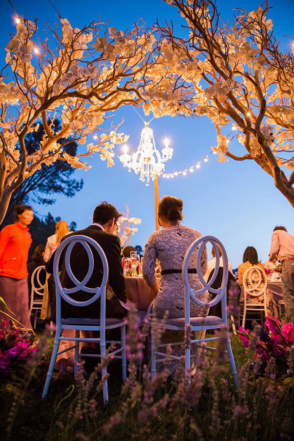A bride and groom at their wedding reception under elegant magical lighting at their Calistoga destination wedding by Destination wedding planner Mango Muse Events