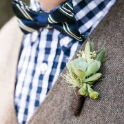 A dressed up groomsmen and his succulent boutonniere