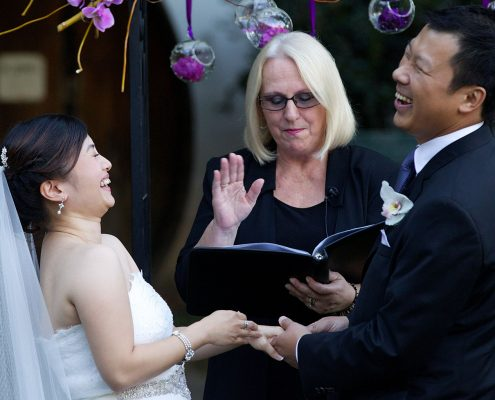Bride and groom laughing during their wedding ceremony by Destination wedding planner, Mango Muse Events