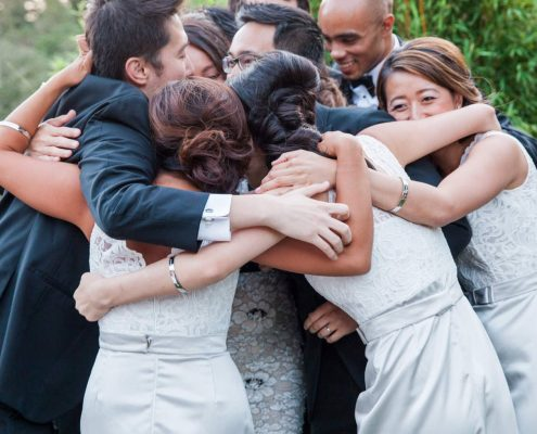Wedding party taking a moment and hugging at a Calistoga destination wedding by Destination wedding planner, Mango Muse Events