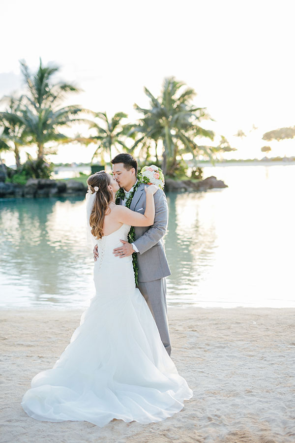 Bride and groom kissing on the beach at their Hawaii destination wedding planned by Destination wedding planner, Mango Muse Events