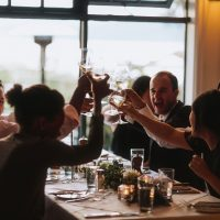 Happy guests clinking glasses at a destination wedding reception in Vancouver by destination wedding planner, Mango Muse Events