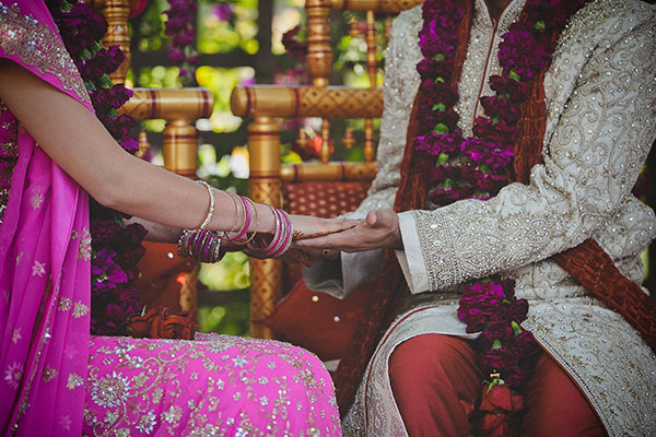 Bride and groom holding hands in a traditional Hindu ceremony at their multi-cultural wedding by Destination wedding planner, Mango Muse Events