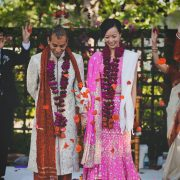 Bride and groom in traditional Indian wedding attire after their wedding ceremony at Los Altos History Museum. Event design by destination wedding planner of Mango Muse Events.