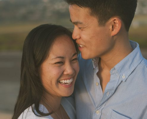 Newly engaged couple smiling at their engagement shoot