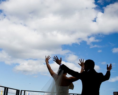 Bride and groom shouting from the rooftops on their wedding day in San Francisco planned by Destination wedding planner, Mango Muse Events