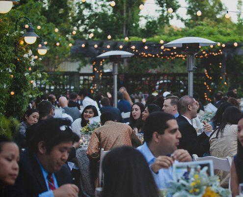 Wedding guests enjoying dinner at an outdoor wedding reception in Los Altos by destination wedding planner, Mango Muse Events